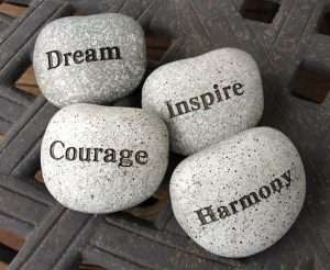 Four pebbles displaying Dream, Inspire, Courage and Harmony